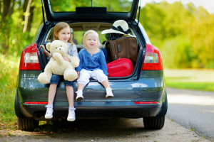 Two adorable little sisters sitting in a car just before getting to visit their Grandparents