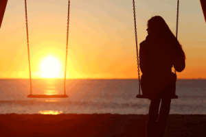 woman alone on a swing at sunset after divorce