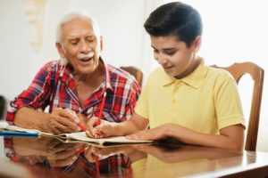 Grandpa helping his grandson with homework at the kitchen table. Grandparents' rights.