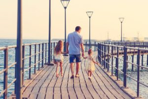Father walking with his daughters on a dock. Learn more about men's divorce issues in New Mexico