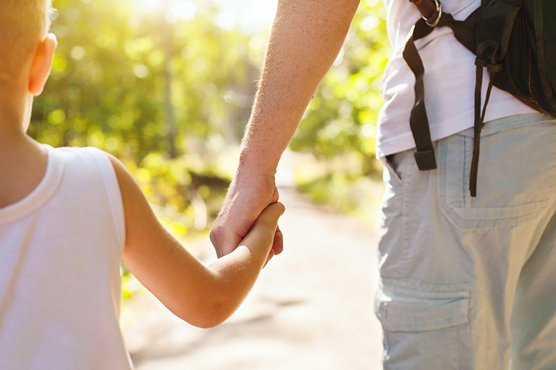 Father and child holding hands. Child custody in New Mexico